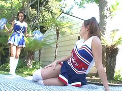 Stunning coed lesbians in cheerleader uniforms having sex outdoors