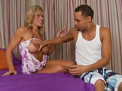 High-heeled blonde cougar with big fake tits enjoying a hardcore interracial fuck