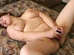 Chubby Julya is lying and masturbating on the bed