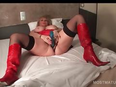 Busty mature in boots pleasuring cunt with sex toy