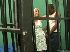 Tattooed blonde rides big black cock in a prison cell