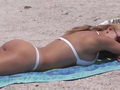 A perfectly shaped blonde shows her boobs on a beach