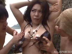 Chubby Japanese girl with big tits enjoying a hardcore gangbang on a beach